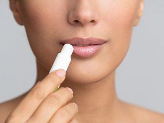 woman applying chapstick as budget lip primer