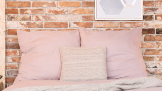 Bed with pillows to represent DIY sweater pillows.