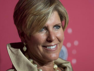 Close-up of Suze Orman in front of a pink background.