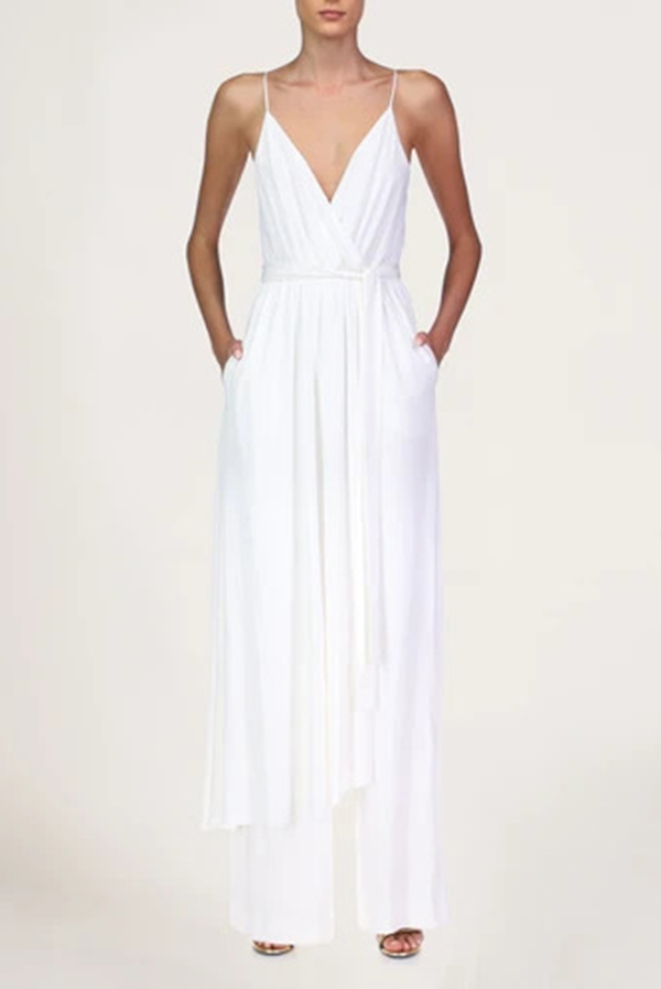 Woman wearing white satin jumpsuit by Halston.