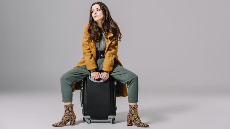 Woman sitting on top of luggage