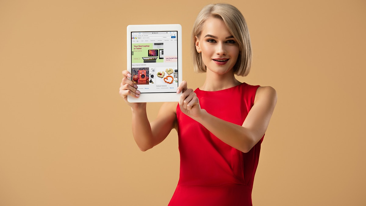 Woman holding up tablet with ebay, one of the most popular clothing auction sites