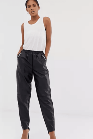 Woman wearing leather joggers and tank top.