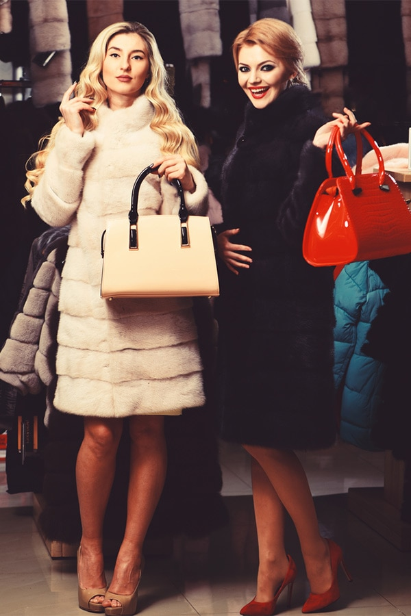 Friends holding designer bags and wearing fur coats