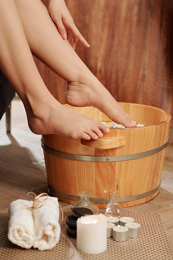 Woman dunking her feet in a basin of water for her at-home pedicure.
