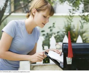 Young Woman Getting Mail From Mailbox