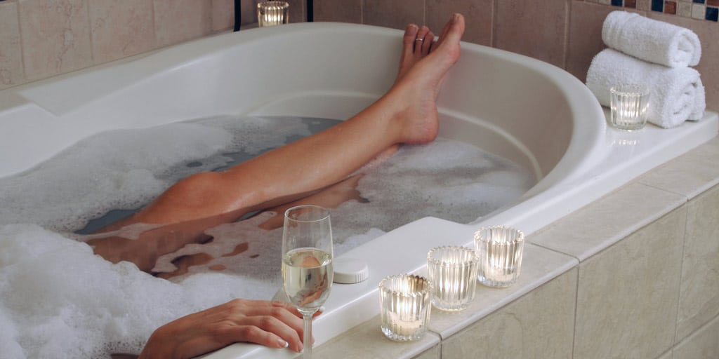 Woman in bath with champagne