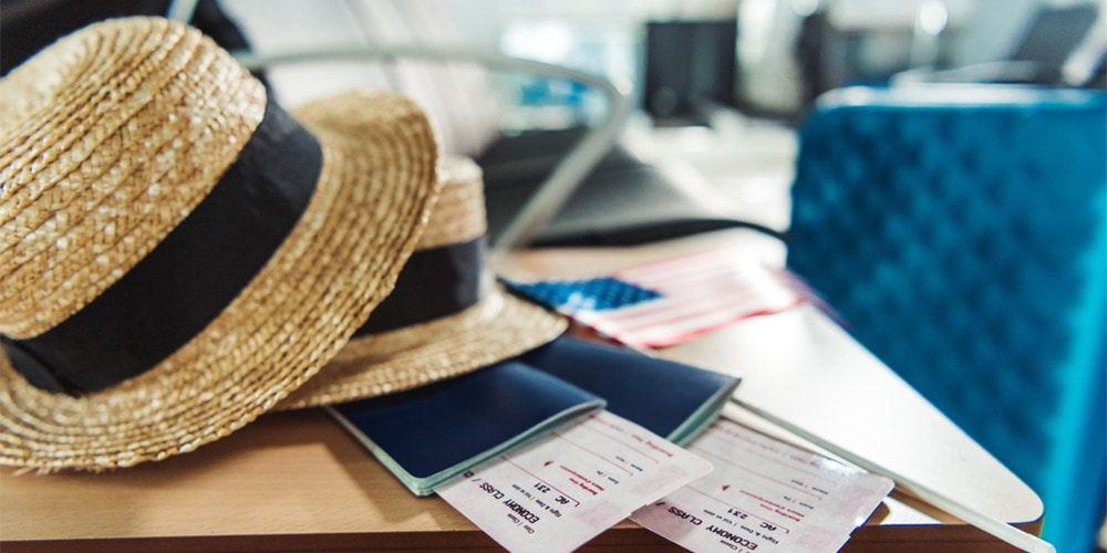 Straw hat and passport on a table in airport
