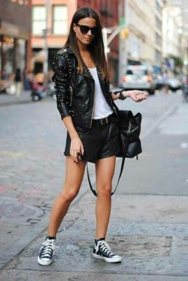 Girl wearing leather jacket, shorts and Converse