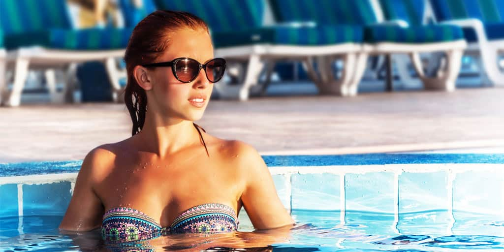 Woman wearing swimsuit and sunglasses in a pool