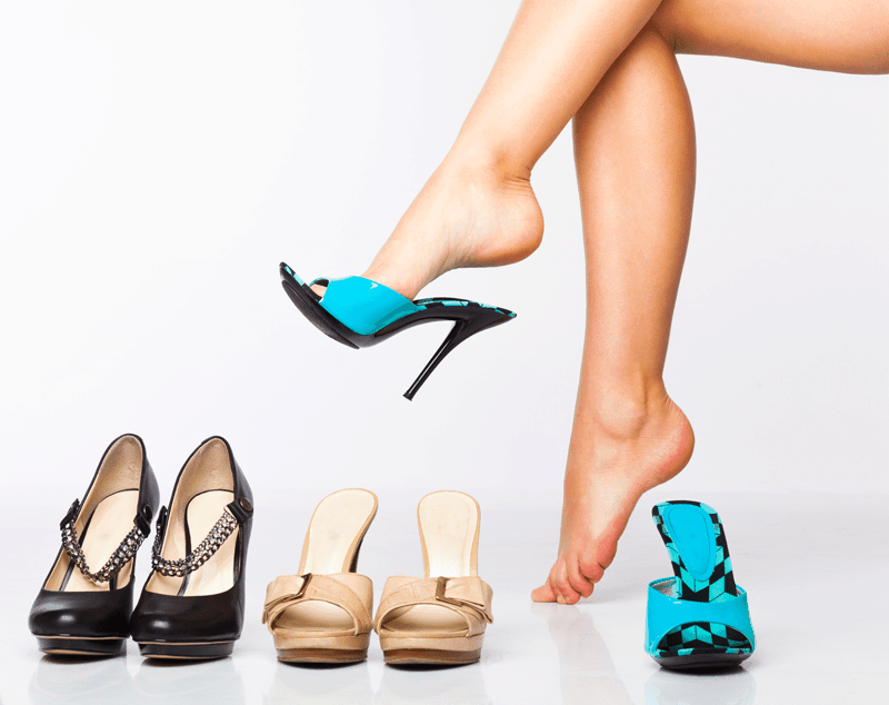 woman's legs with three pairs of shoes