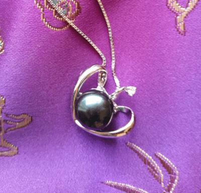 black pearl pendant on purple fabric