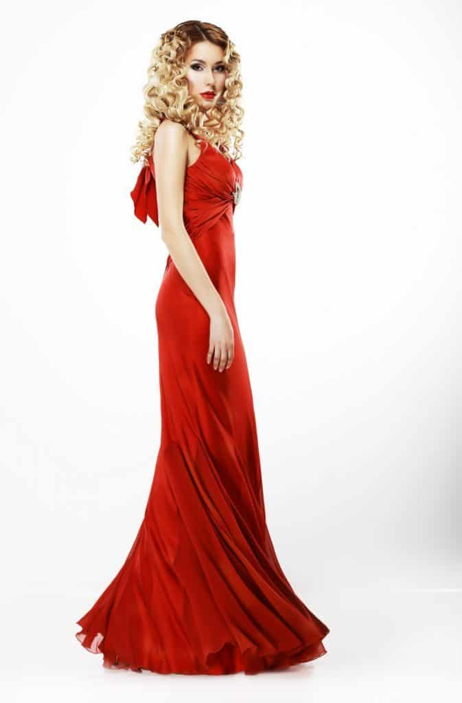 Luxury. Full Length of Elegant Lady in Red Satiny Dress. Frizzy Blond Hair
