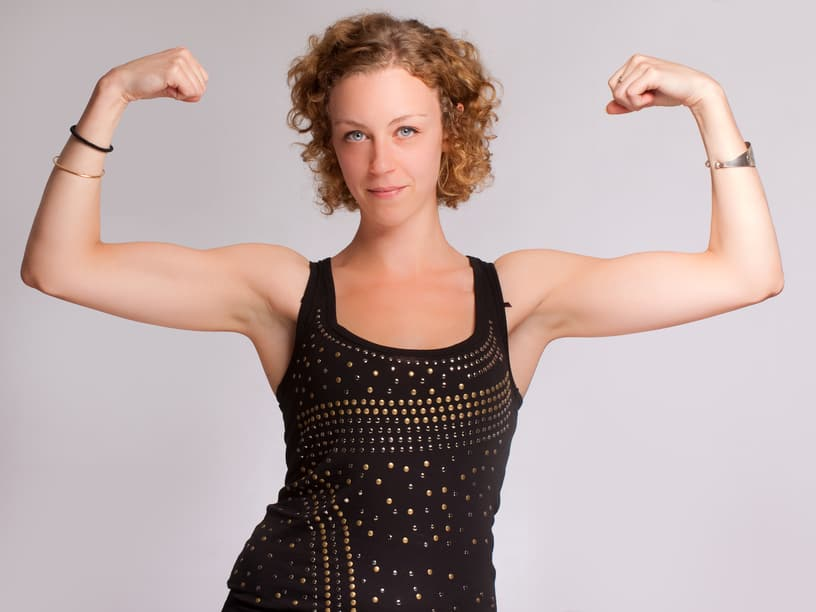 woman holding her arms up to show biceps