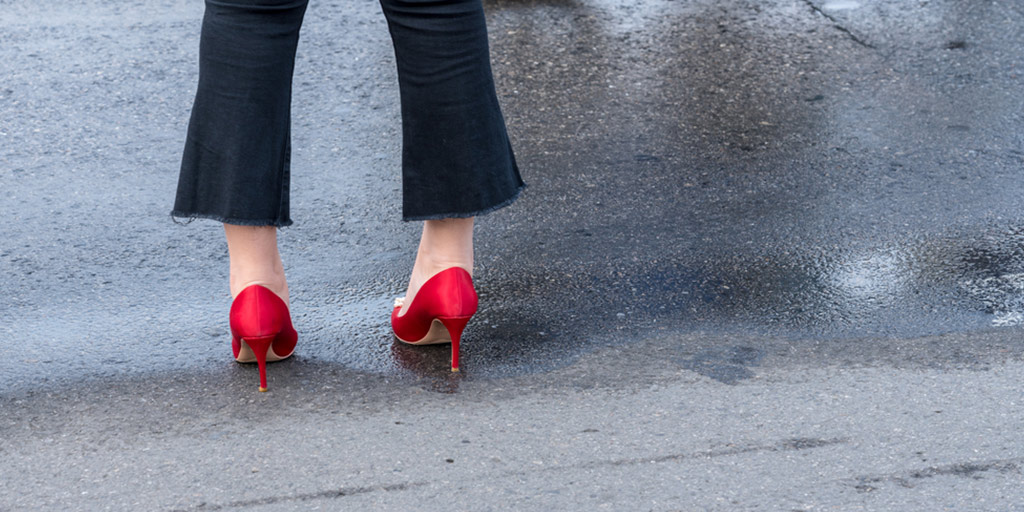 Woman wearing flared jeans and red heels