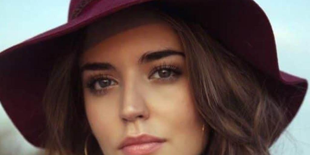 Woman wearing maroon, floppy hat