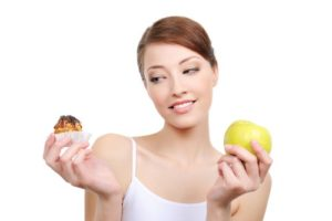 female choice  -  high-calorie cake or healthy apple - white background