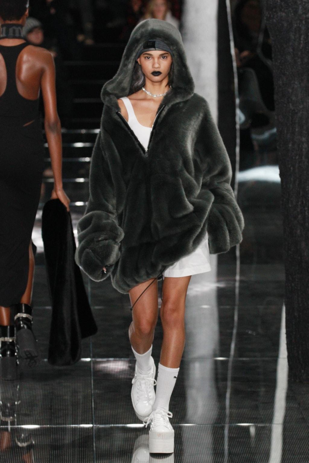 Model on runway wearing fur coat