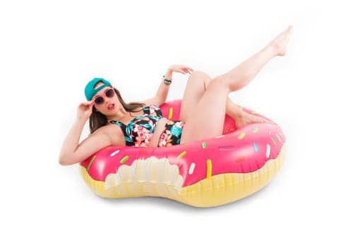 plus-size model wearing swimsuit and sitting on blow up donut