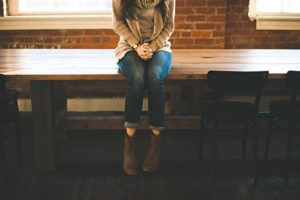 girl wearing jeans sitting on wood table
