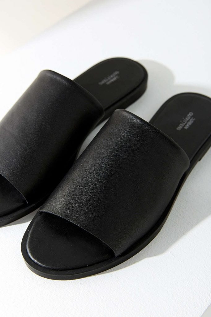 pair of black low heeled leather slides on white background