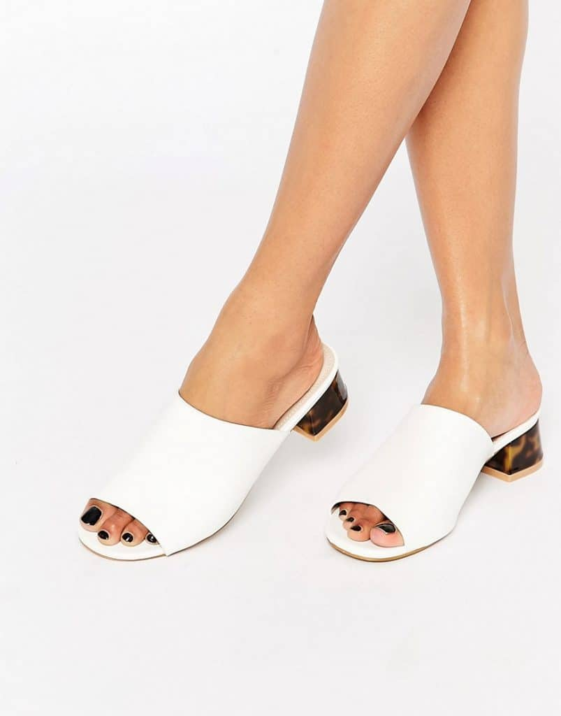 woman's bare legs from mid calf wearing white low-heeled mule sandals