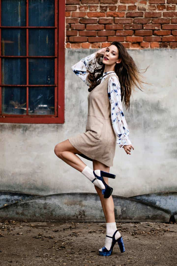 Woman wearing beige jumper dress with floral blouse