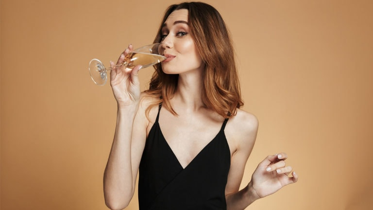 Woman drinking champagne in black dress
