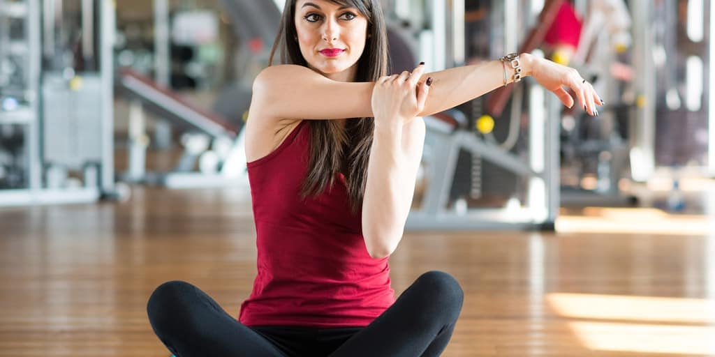 Woman stretching in gym wearing red tank top