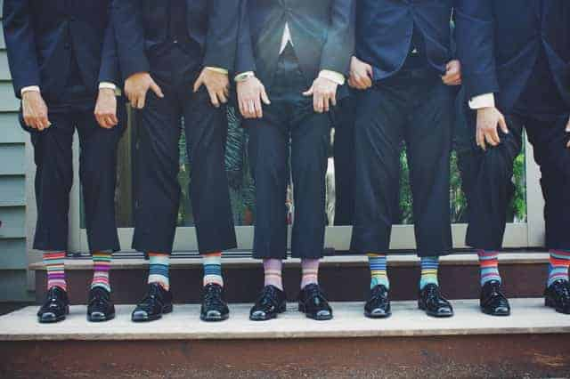 men in suits wearing colorful socks
