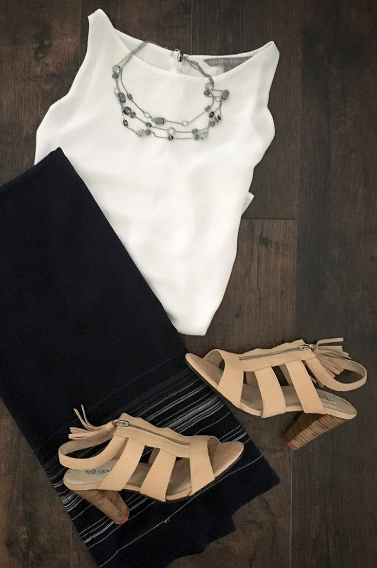 Sshoes are the solution to loud heels. Here, they're styled with a midi skirt, white blouse and statement necklace.