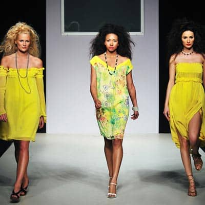 Three models wearing bright yellow dresses walking on the runway.