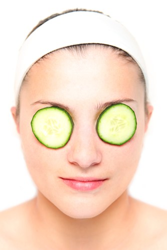 Woman with cucumber slices on her eyes