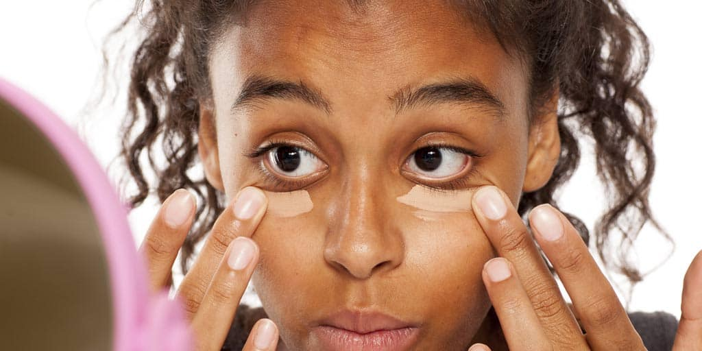 Woman putting on concealer over puffy eyes.