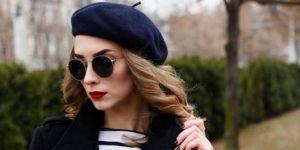 Woman wearing sunglasses and stylish navy blue beret