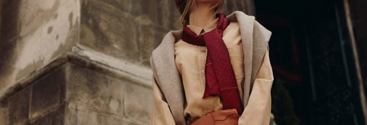 Woman wearing warm-toned layered outfit with scarf.