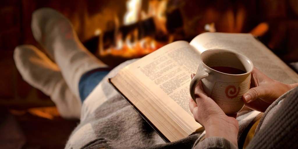 Women lounging by the fire with a blanket and good book
