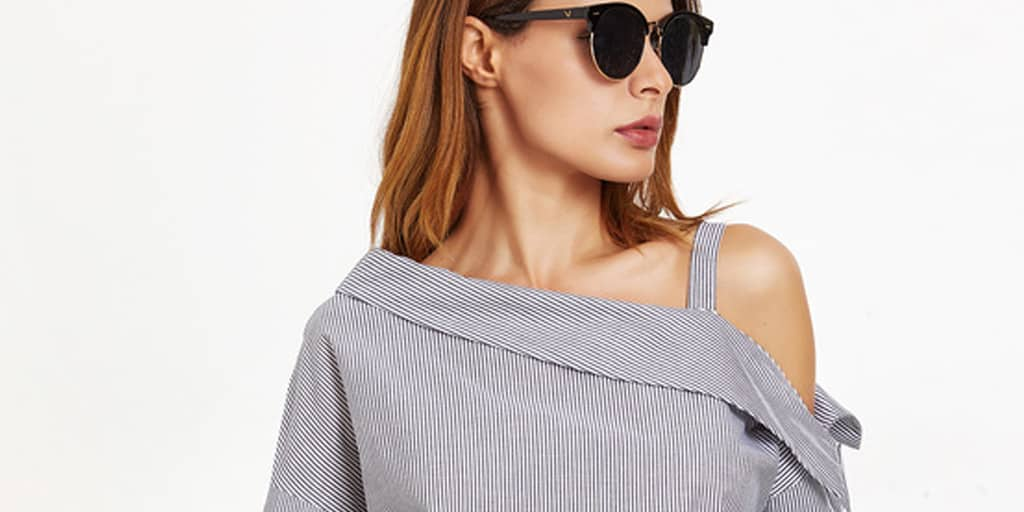 Woman wearing sunglasses and pinstriped, asymmetrical top
