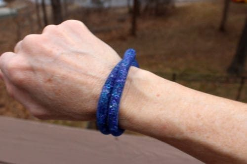 Wrist showing off a double-wrapped blue bracelet