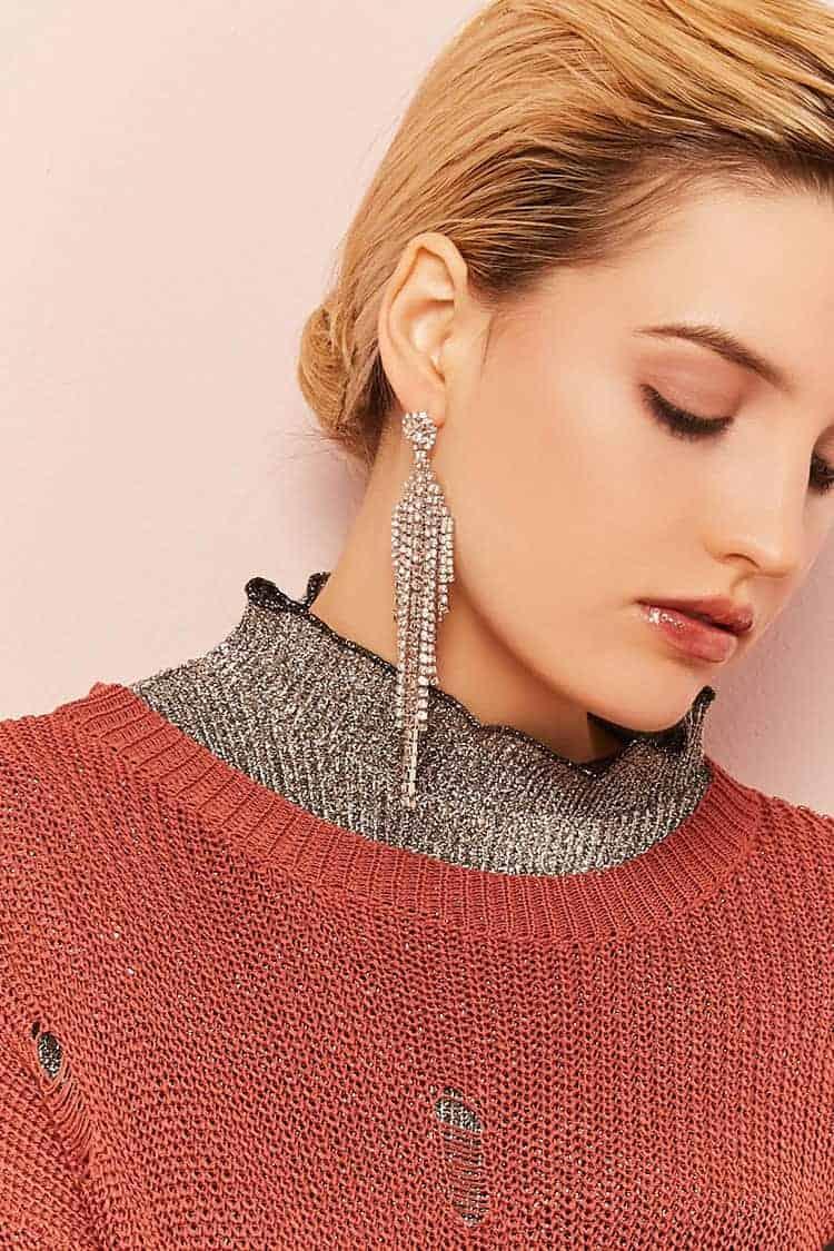 Woman wearing long chandelier style rhinestone earrings