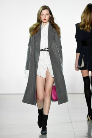 Runway model wearing gray trenchcoat and white shirt dress