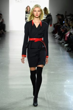Runway moel waring dark suit with red belt and red collar