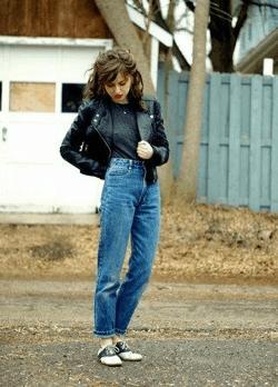 Brunette wearing leather jacket, black t shirt, denim and saddle shoes
