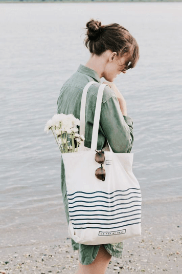 Girl on beach holding striped canvas tote