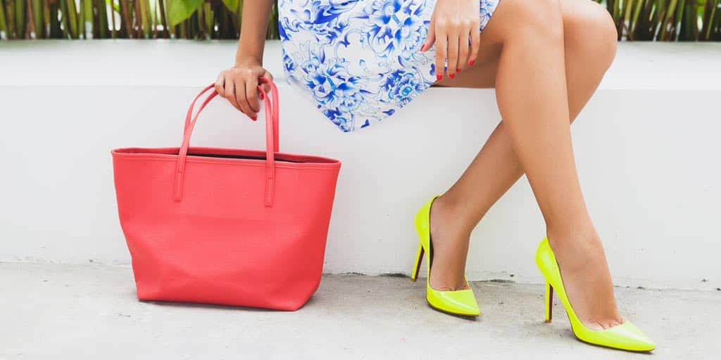 Woman sitting on a step with red bag and yellow heels