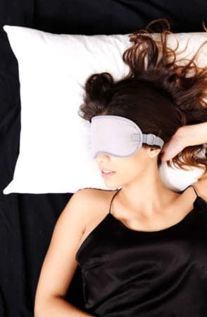 Woman sleeping in bed with eyemask