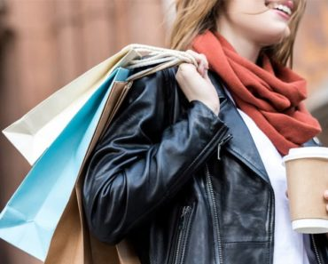 Woman wearing leather jacket with shopping bags