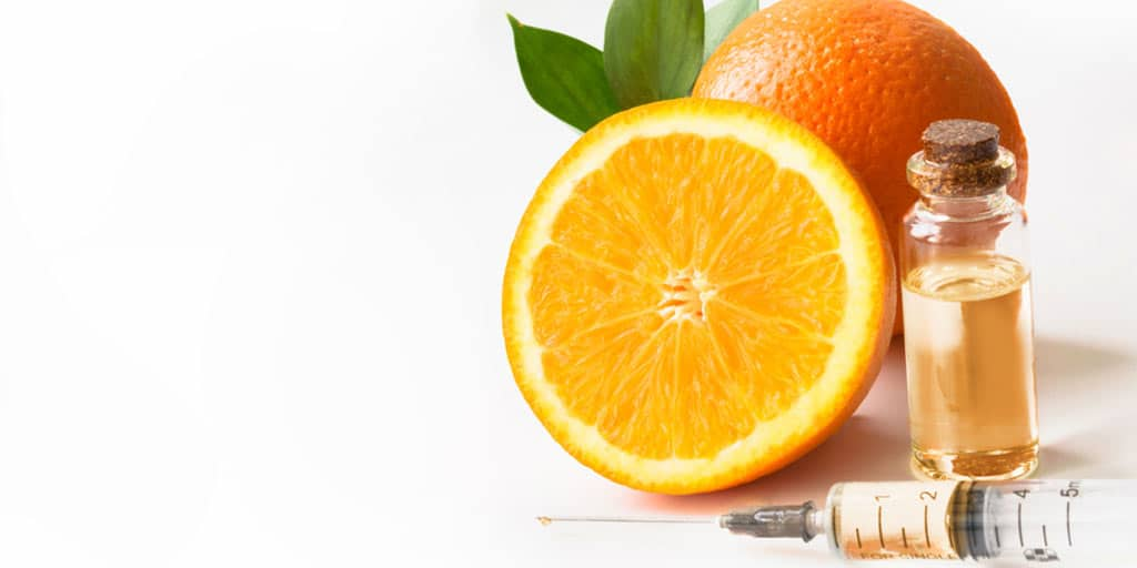 Orange and vial of vitamin C serum