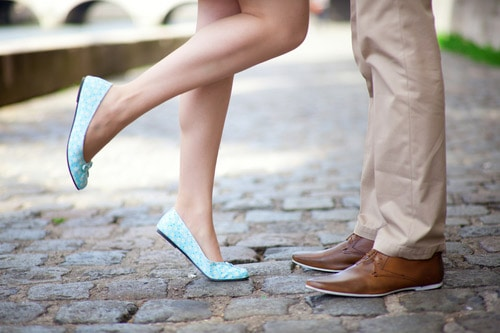 Woman and man from knees down standing on sidewalk