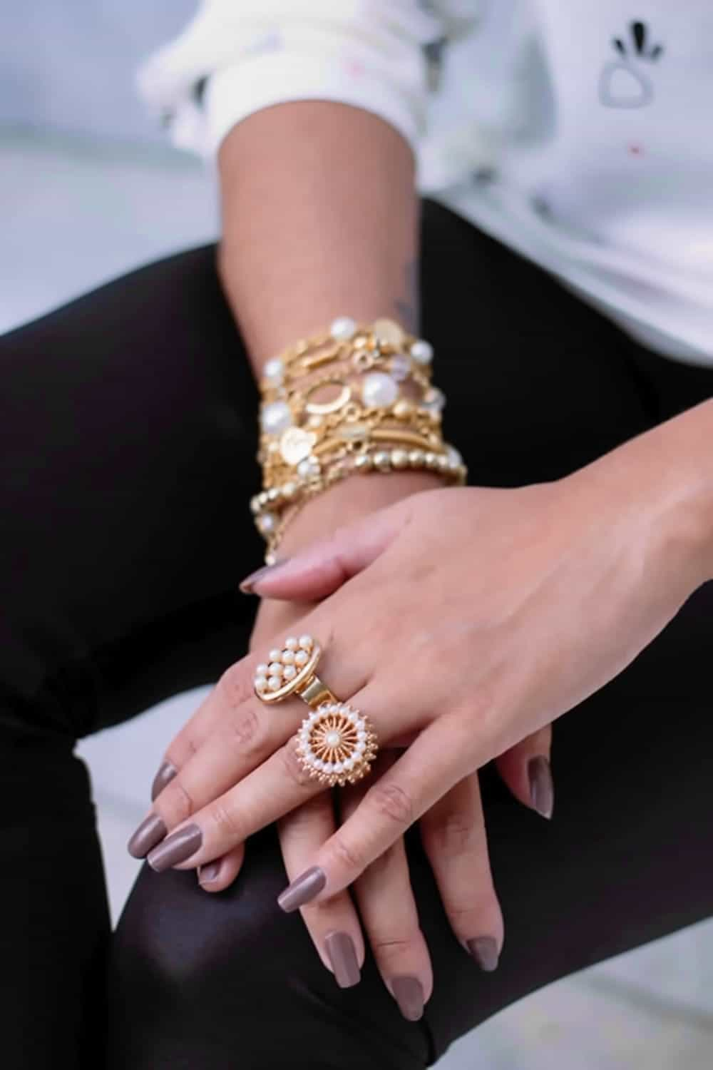 Close up of woman's hands with stacked rings and bracelets